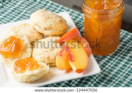 Biscuits and fresh peach jam on a white plate - stock photo