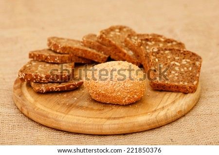 Biscuits baked from flour and bran. Cut pieces of black crusty bread. Diet bread useful for a healthy diet. Different types of bread is piled on the table in the composition. White and brown bread. - stock photo