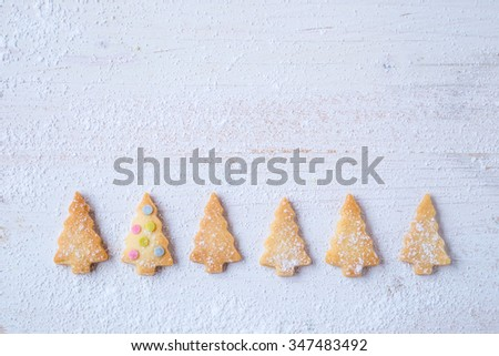 biscuits in form of fir trees decorated with sugar confetti - stock photo