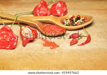 Bishop's crown chilli peppers and tomato spicy hot chili pepper sauce in a wooden spoon on the wooden background  - stock photo
