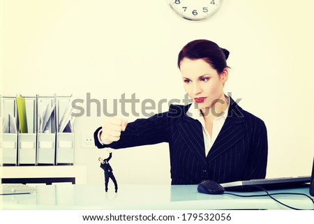 Bisnesswoman holding her fist bayond a miniature of a worker she wants to destroy. - stock photo