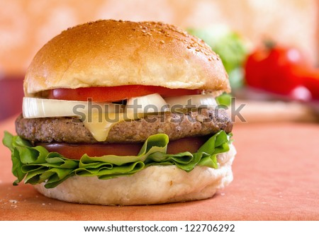 Bison Cheeseburger on table with some blurred vegetables. On location shot. - stock photo