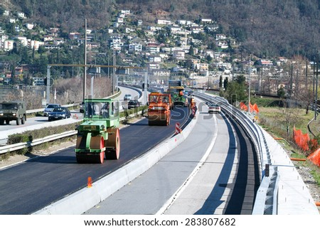 Bissone, Switzerland - 8 March 2007: Workers and vehicles during the asphalting of the highway at Bissone on Switzerland - stock photo