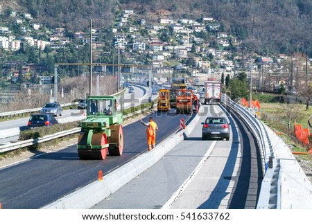Bissone, Switzerland - 8 March 2007: Workers and vehicles during the asphalting of the highway at Bissone on Switzerland