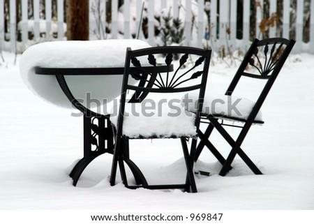 Bistro Set Melting - garden furniture melting after a snowstorm. - stock photo