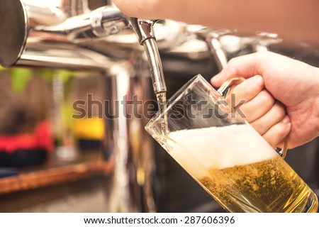 bistro waiter serving a cold, chill beer. Hand of barman pouring a lager beer from tap - stock photo