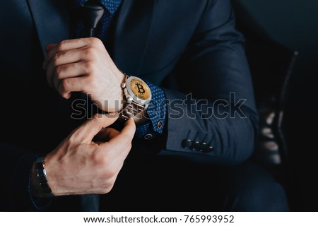 Bitcoin watch. Close-up of gold bitcoin is embedded in clock face of businessman. Concept time is money online