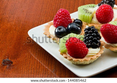 bite size fruit tarts with fresh fruit served on a white plate