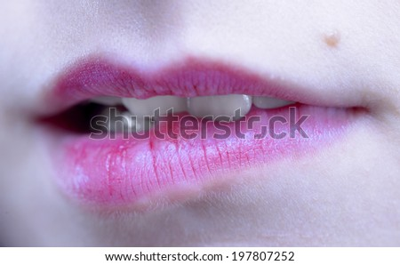 Biting her red lips teeth - stock photo