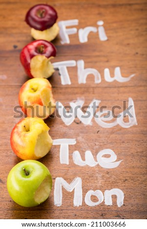 Bitten apples next to days of the week: health eating concept - stock photo