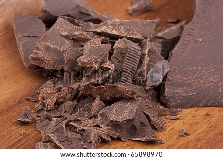 Bitter chocolate in pieces on a brown background in a plate. - stock photo