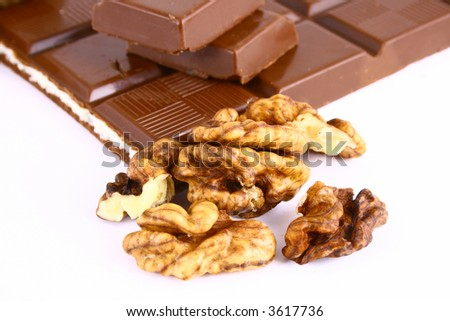 Bitter dark chocolate in a foil and nuts on black background