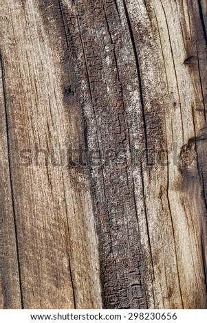 Bituminous surface texture of an old weathered, rotten, cracked Square Timber Bollard, made of obsolete, scrapped Railroad Cross Tie Timber. - stock photo