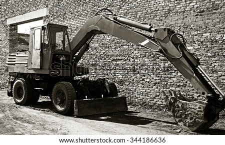 BIYSK, RUSSIA - MAY 29, 2010: Old excavator with bucket against the background of a brick wall - stock photo