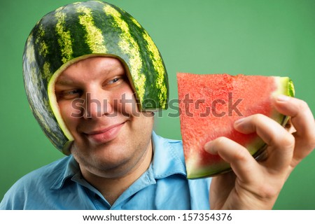 Bizarre man in a helmet from a watermelon preparing to eat - stock photo