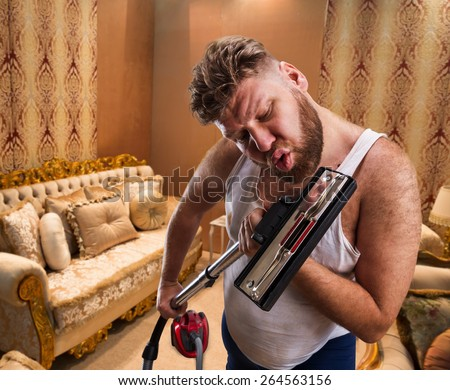 Bizarre man with beard sings to the vacuum cleaner at home interior - stock photo