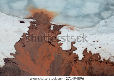 Bizarre streams of bright red clay on  ice of  lake near shore.  - stock photo