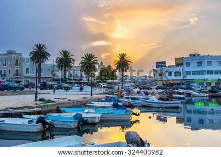 BIZERTE, TUNISIA - SEPTEMBER 4, 2015: The beautiful sunset over the old port reflects in water, on September 4 in Bizerte.