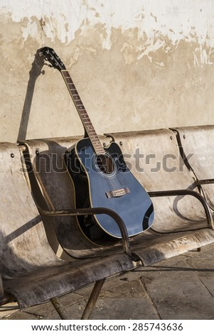 Black acoustic guitar on the old shabby chairs - stock photo