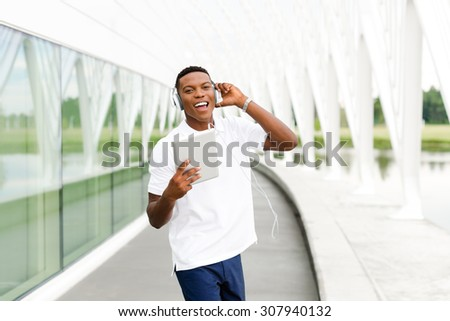 Black, African American college student wearing headphones and listening to music on a digital tablet computer - stock photo