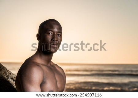 Black african american male, fashion model on the beach during sunset, next to a rock - stock photo