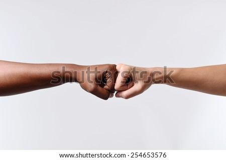 black African American race female hand touching knuckles with white Caucasian woman in agreement partnership and cooperation multiracial diversity immigration concept - stock photo