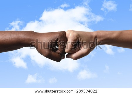 black African American race female hand touching knuckles with white Caucasian woman in agreement partnership and cooperation multiracial diversity immigration concept blue sky background - stock photo