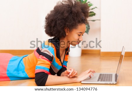 Black African American student teenage girl with a afro haircut seated on the floor using a laptop computer - stock photo