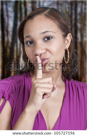 Black African American woman saying be quiet by saying shhh - stock photo