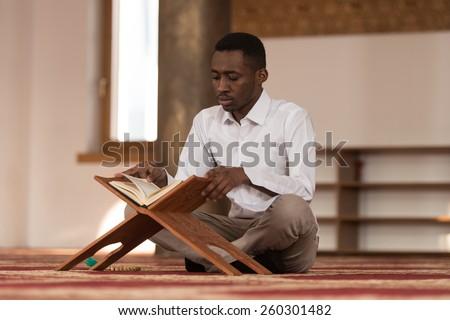 Black African Muslim Man Is Reading The Koran - stock photo