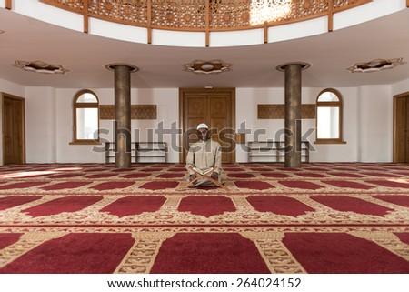 Black African Muslim Man Reading Holy Islamic Book Koran - stock photo