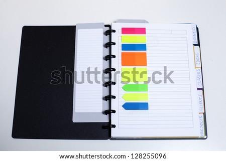 Black agenda with organizing colored elements/Perfectly organized - stock photo