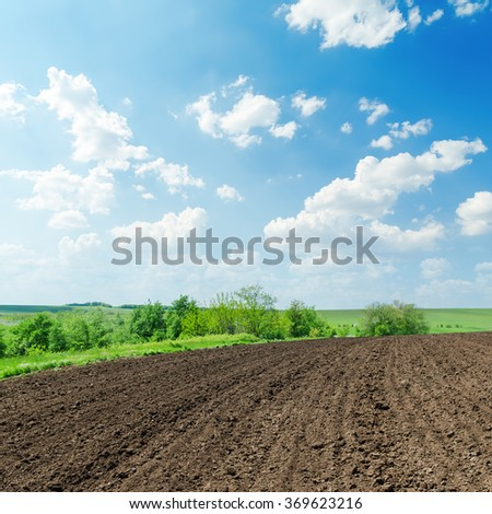 black agriculture field and white clouds in blue sky on spring - stock photo