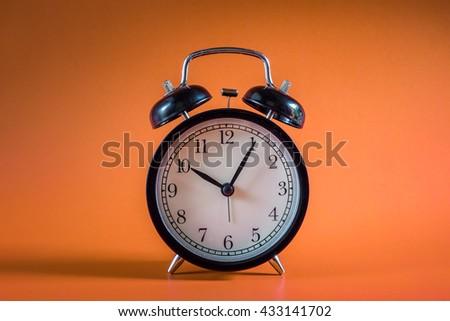 Black alarm clock on Orange background. clock concept. Alarm clock at ten o'clock five minute. - stock photo