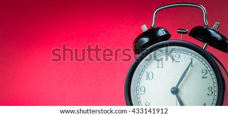Black alarm clock on red background. clock concept. Alarm clock at five o'clock five minute. - stock photo