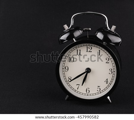 Black alarm clock on textile background