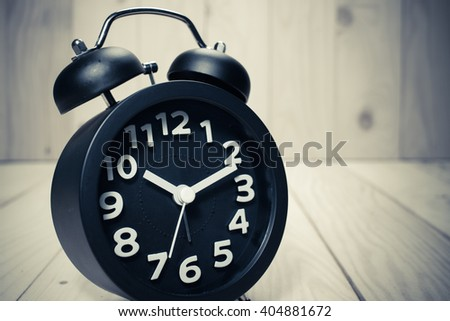 Black alarm clock  on wood background / vintage tone