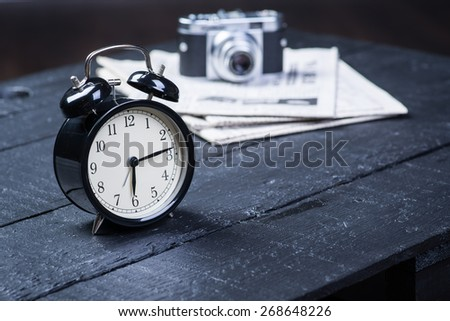 Black alarm clock with camera and newspaper on a wooden table - stock photo