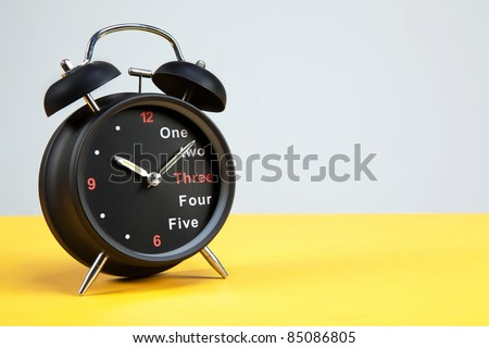 Black alarm clock with yellow and grey background - stock photo