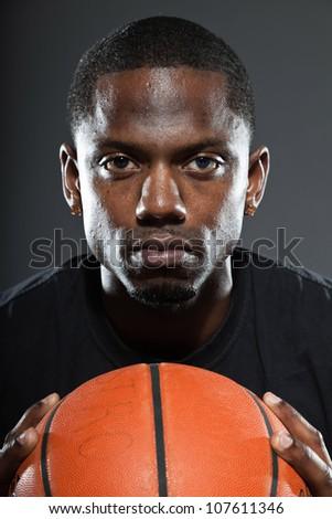 Black american basketball player. Studio portrait isolated on grey background. - stock photo