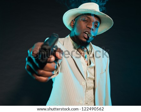 Black american mafia gangster man in suit with pistol. - stock photo