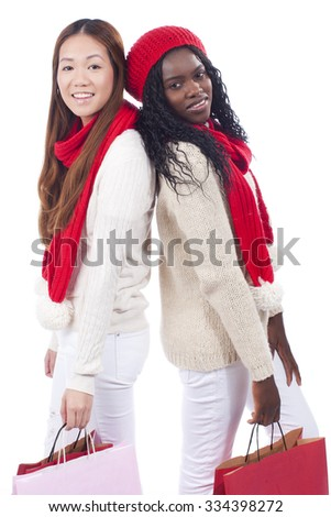 Black and asian woman with shopping bags on christmas isolated
