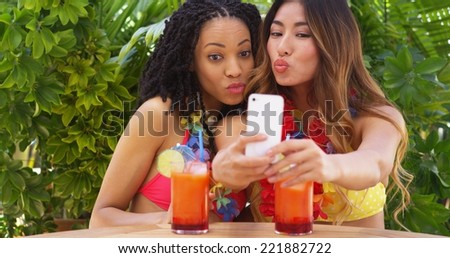 Black and Asian women taking selfie while on tropical vacation - stock photo
