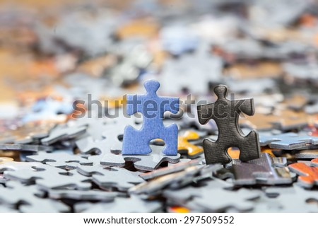 Black and blue puzzle pieces on a pile of jigsaw pieces. Shallow depth of field - stock photo