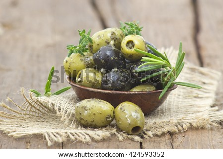black and green olives marinated with garlic and fresh mediterranean herbs - stock photo