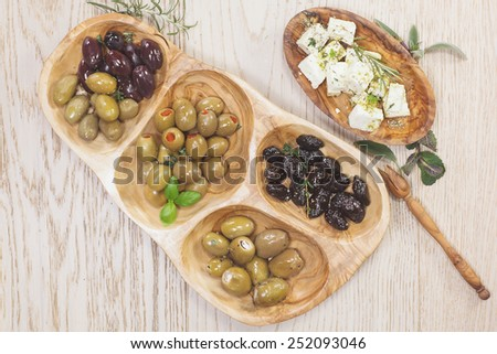 Black and green olives with feta cheese. Assorted olives and feta or goat cheese cheese in olive tree dish on wooden table - stock photo