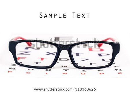 Black and red reading glasses kept over black and red eye chart with copyspace for text.