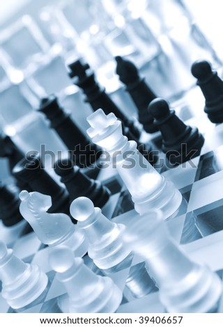 Black and transparent white pieces of chess on chess board made of glass - stock photo