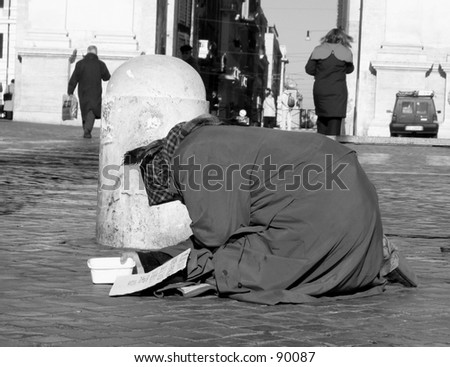 Black and White: a beggar woman bowing for a coin at piazza del popolo Rome.