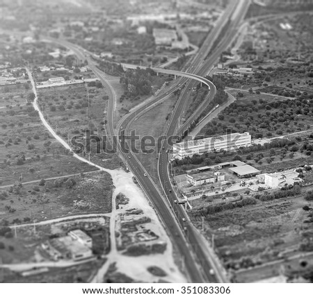 Black and white aerial view of the road. Tilt-shift effect. - stock photo